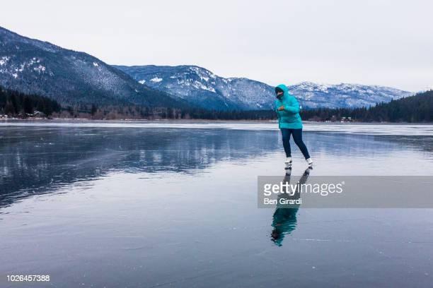 woman ice skating on frozen alta lake, whistler, british columbia, canada - eislauf oder rollschuhlauf stock-fotos und bilder