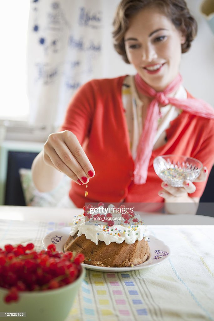 Woman icing a cake in kitchen : Stock Photo