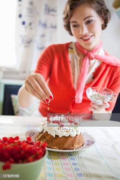 Mujer la cubierta de crema de una torta en la cocina