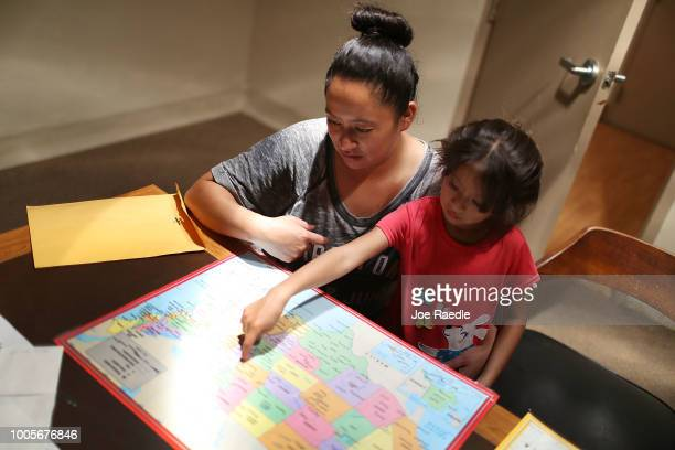 A woman identified only as Heydi and her daughter Mishel look at a map of the United States as they figure out where their sponsor lives as they stay...