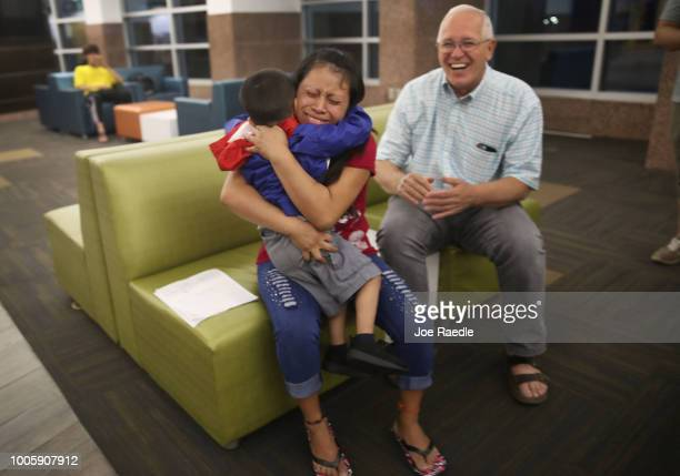 A woman identified only as Maria is reunited with her son Franco as Ruben Garcia director of the Annunciation House happily looks on at the El Paso...