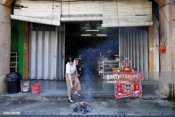 A woman ignites a fire in front of a shop during Chinese New Year celebration in Kuala Lumpur Malaysia on February 5 2019 Malaysian government set...