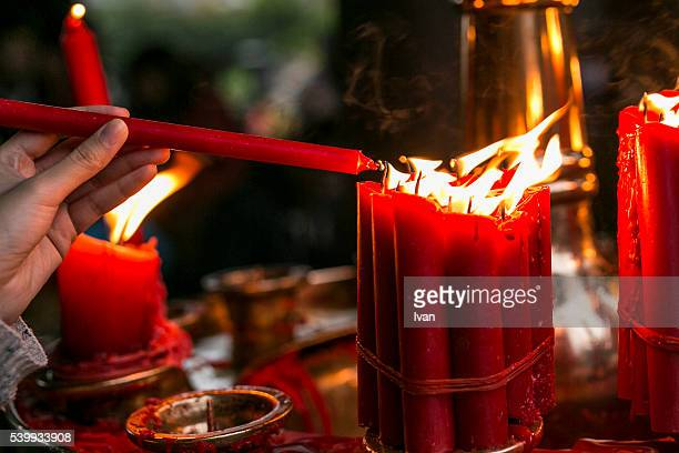 A Woman Igniting a Burning Red Candle in Traditional Chinese Temple