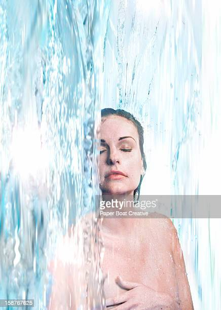 Woman immersed in a waterfall