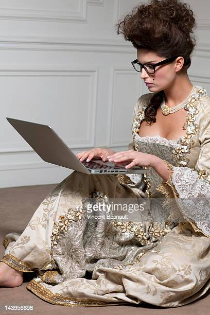 A woman in 18th century costume using a laptop