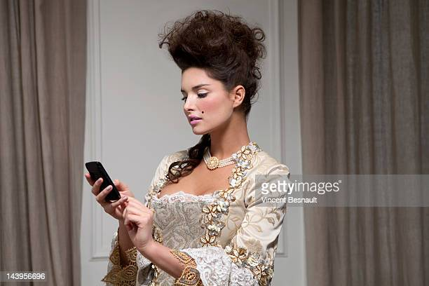 A woman in 18th century garb using a smart phone
