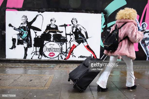 A woman in 1970's clothing walks past a satirical piece by artist Loretto featuring Queen Elizabeth II German Chancellor Angela Merkel and British...