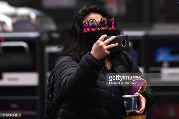 Woman in 2021 glasses takes a photo of the New Year's Eve numerals on display in Times Square on December 21, 2020 in New York City. The...