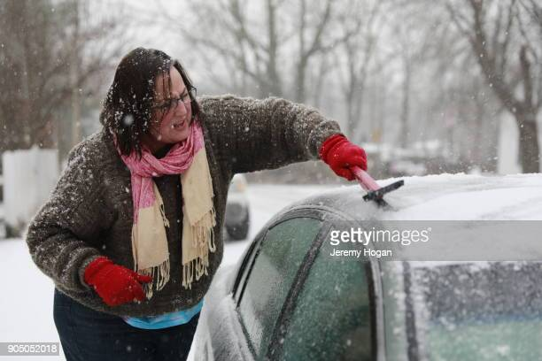 woman in 50s scraping ice off car in snow - bloomington indiana stock photos and pictures