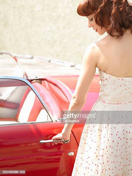 Woman in 50's style dress  opening vintage car door