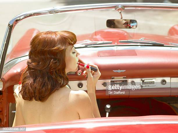 Woman in 50's style dress  putting on lipstick in vintage car