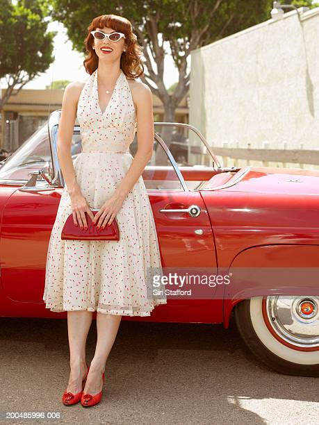 Woman in 50's style dress  standing next to vintage car