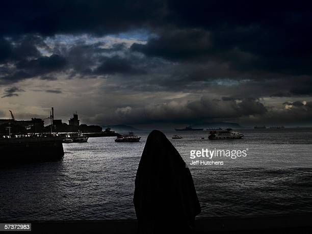 A woman in a abaya stands overlooking the water by the Gateway Of India on September 10 2005 in Mumbai India Emerging from one of the most deadly...