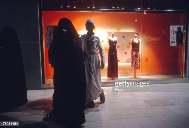 A woman in a abaya walks in front of a storefront window displaying westernized fashions at the Kingdom Centre's shopping center on January 2003 in...