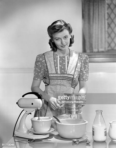 Woman In A Apron Over A Cotton Print Dress Sifting Flour In A Bowl Between A Mixer & A Quart Of Milk Baking Pastry Housewife Baking Cooking Kitchen.