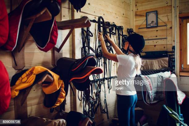 woman in a barn preparing for training - riding hat stock pictures, royalty-free photos & images