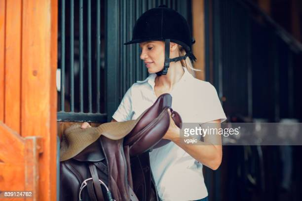 Woman in a barn preparing for training