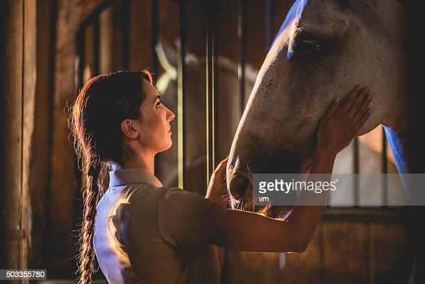 Woman in a barn stroking a horse's head