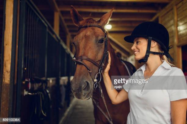 woman in a barn stroking her horse - thoroughbred horse stock pictures, royalty-free photos & images