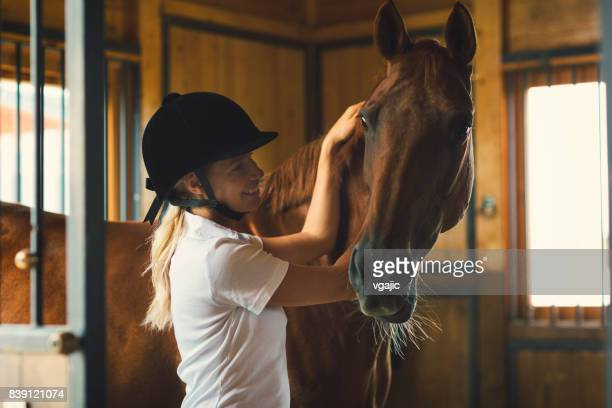 Woman in a barn stroking her horse