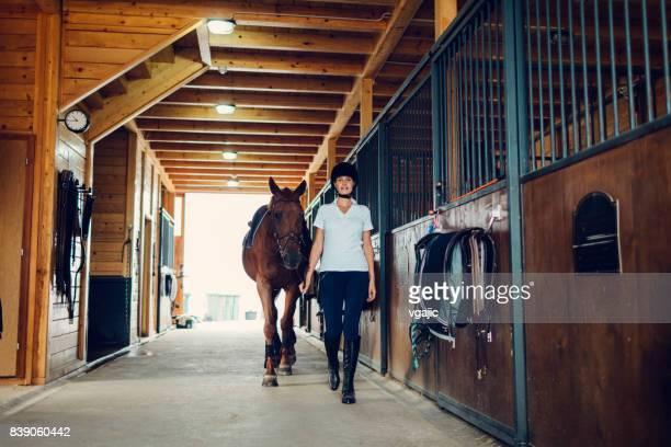 Frau in einer Scheune mit ihrem Pferd