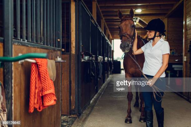 Woman in a barn with her horse