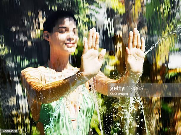 Femme en maillot de bain derrière une chute d'eau
