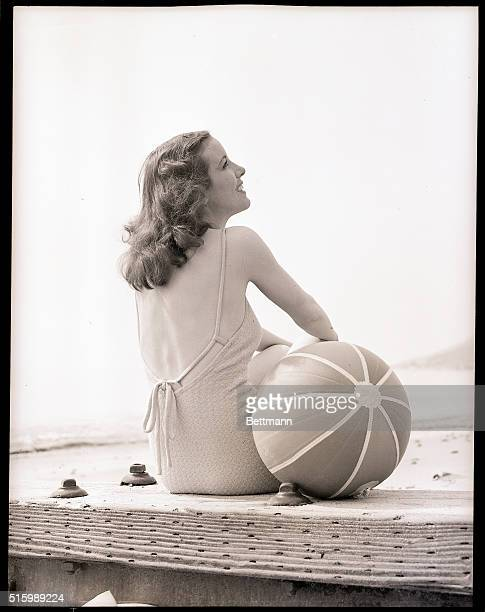 A woman in a bathing suit sits with a beach ball beside her Undated photograph circa 1950's