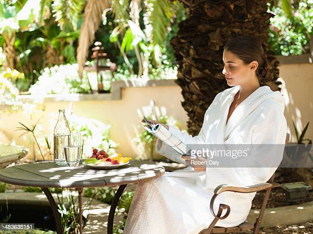 woman in a bathrobe reading a magazine - nature magazine stock pictures, royalty-free photos & images