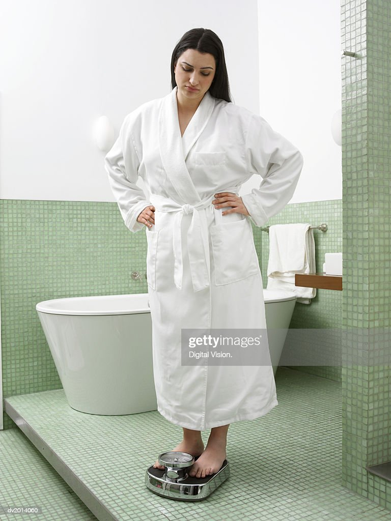 Woman in a Bathroom Weighing Herself on Scales : Stock Photo