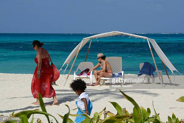 A woman in a bikini sits under the shade of umbrellas with the sea in the background on January 24 2014 in San Andres Colombia Colombia has a...