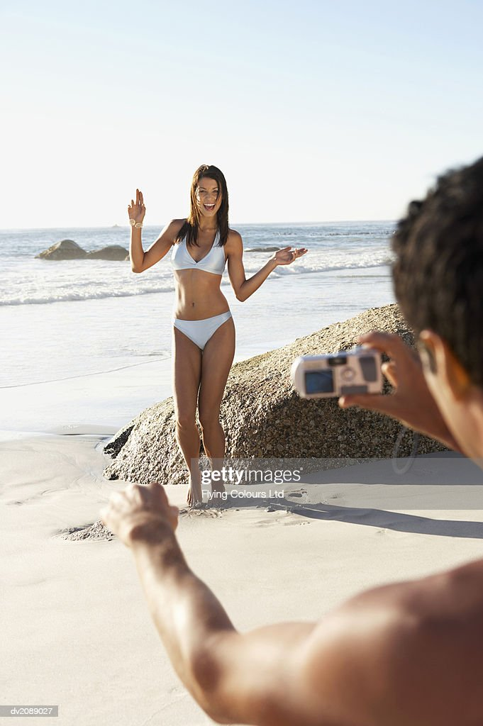 Woman in a Bikini Stands on the Beach, Posing for a Man With a Digital Camera : Stock Photo