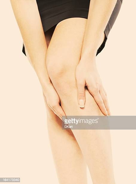 woman in a black dress clutching her knee - feet torture stock pictures, royalty-free photos & images