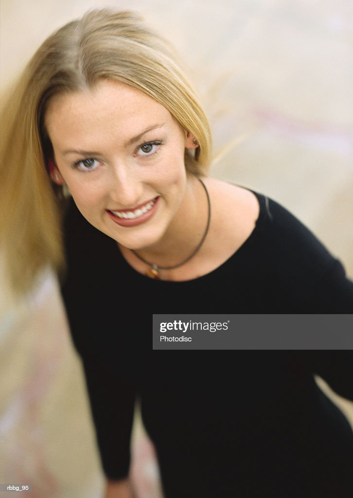 woman in a black dress looking up into the camera or audience and smiling while she spins around creating a blur of motion : Stock Photo