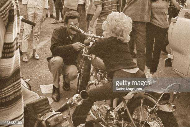 Woman in a bleached, boufant hair-do, sitting on a motorcycle, seen from behind at the 1st Elysian Park Love-In on March 26, 1967 in Los Angeles,...