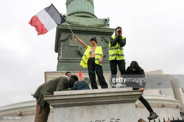 A woman in a bra wearing a quotyellow vestquot and holding a French flag demonstrate perched on a pillar in the base of the Colonne de Juillet in...