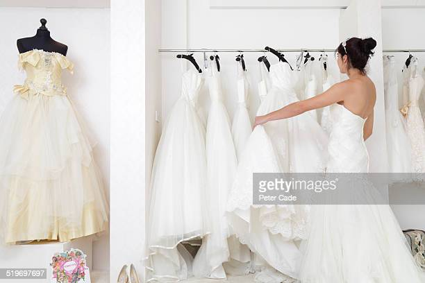 woman in a bridal shop looking at wedding dresses. - wedding dress stock pictures, royalty-free photos & images