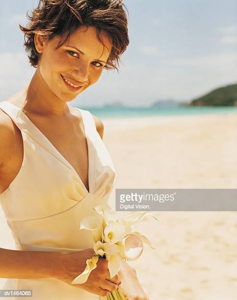 woman in a bridesmaid dress stands holding a bouquet of lillies on a sandy beach - une seule jeune femme photos et images de collection