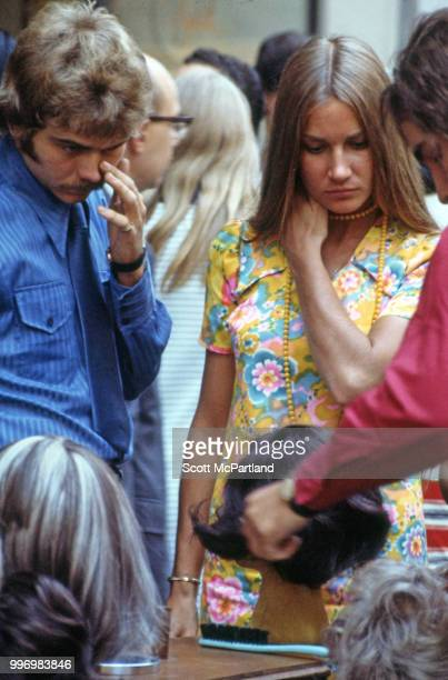A woman in a brightly colored dress pauses to look at a sidewalk vendor's display of wigs on an unidentified crowded Manhattan street New York New...