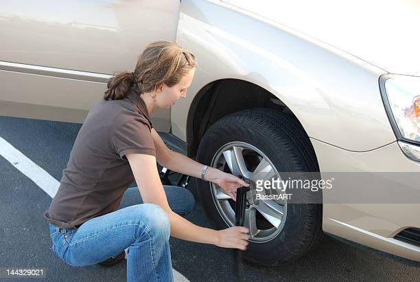 woman in a brown shirt and jeans changing a tire - flat tire stock pictures, royalty-free photos & images