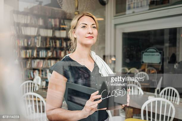 Woman in a cafe attaching closed sign to glass pane
