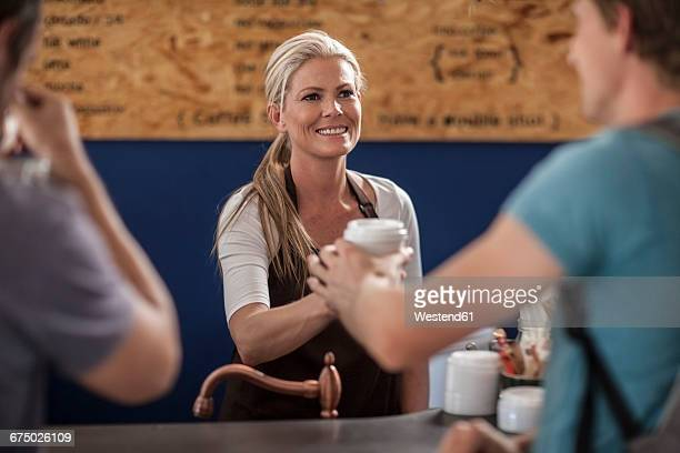 Woman in a cafe handing over disposable coffee cup
