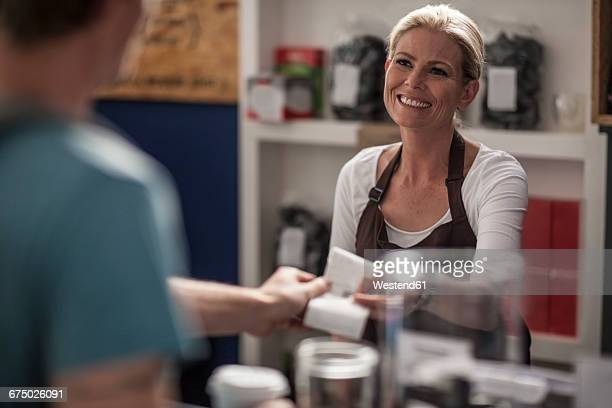 Woman in a cafe handing over receipt to customer