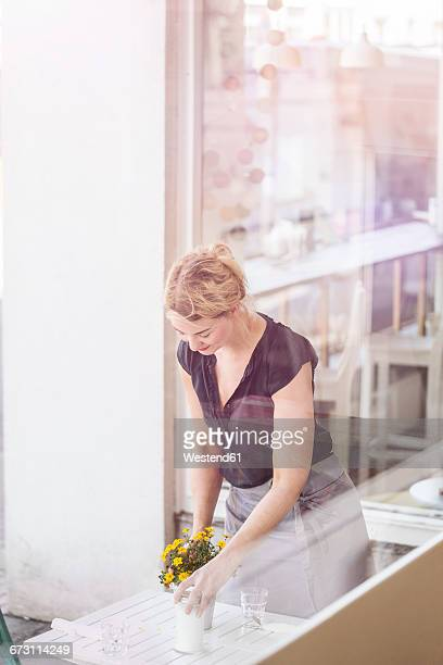 Woman in a cafe placing flowers on table