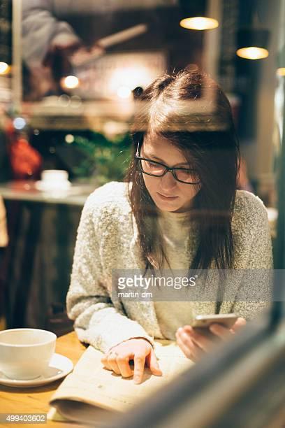 Femme dans un café vous recherchez un emploi dans un journal