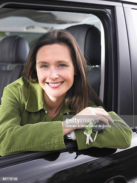 Woman in a car, holding keys, smiling