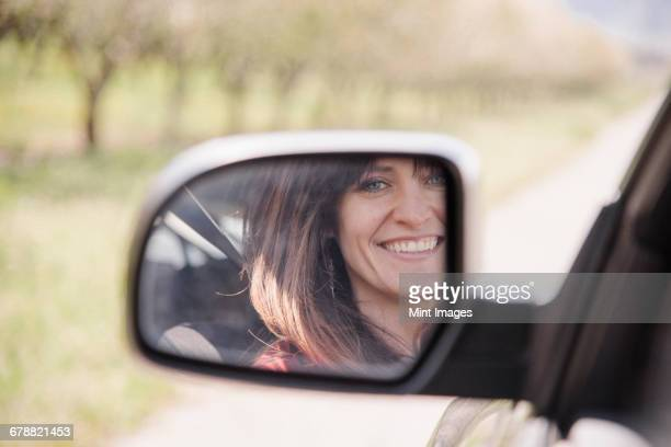 Woman in a car, smiling at her reflection in the side mirror.