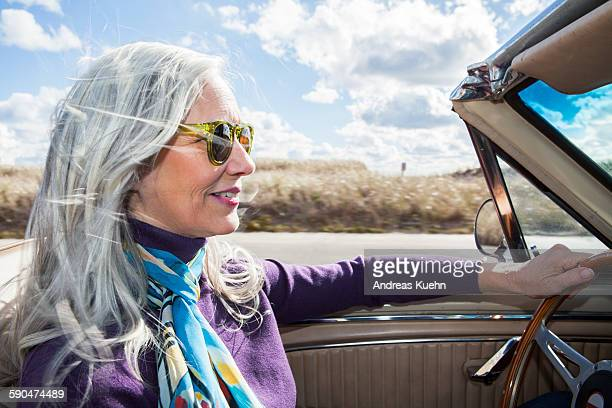 Woman in a car with her hair blowing in the wind.