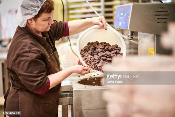 woman in a chocolate manufacture filling machine with chocolate pieces - chocolate factory stock pictures, royalty-free photos & images