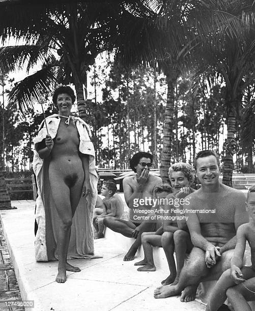 A woman in a crown and cape a staff in her hand poses beside a swimming pool at an unidentified camp watched by other nudists men women and children...